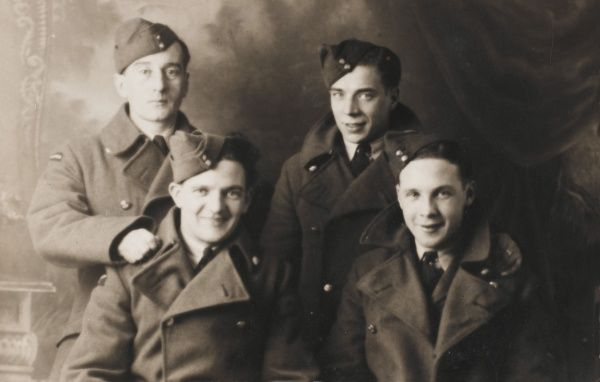 Four British airmen in uniform pose for their photo in the photographer's studio