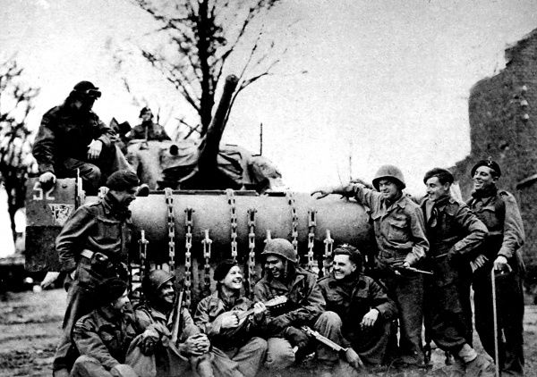 Photograph showing British and American troops having a 'sing-song' in front of a Sherman 'Flail' tank, near Geilenkirchen, late 1944