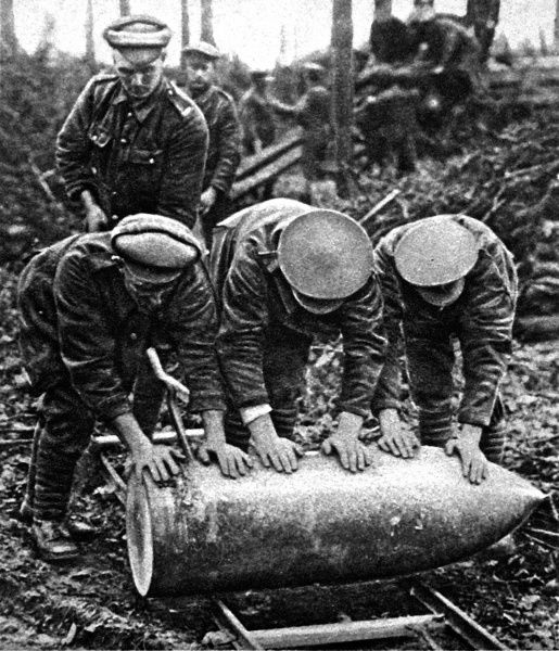 Photograph showing three British artillerymen rolling a large shell towards their gun, Western Front, 1916