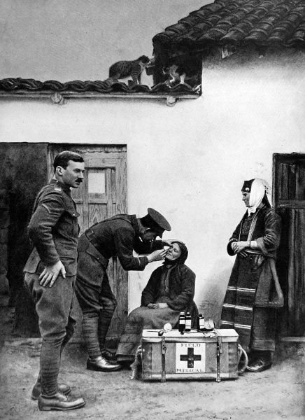 A British Army Doctor assisting a woman with minor injuries. The photograph shows British troops on friendly terms with the Macedonian villagers