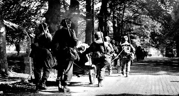 Photograph showing men of the British First Airborne Division marching into Arnhem with their guns and equipment, after landing outside the town, September 1944