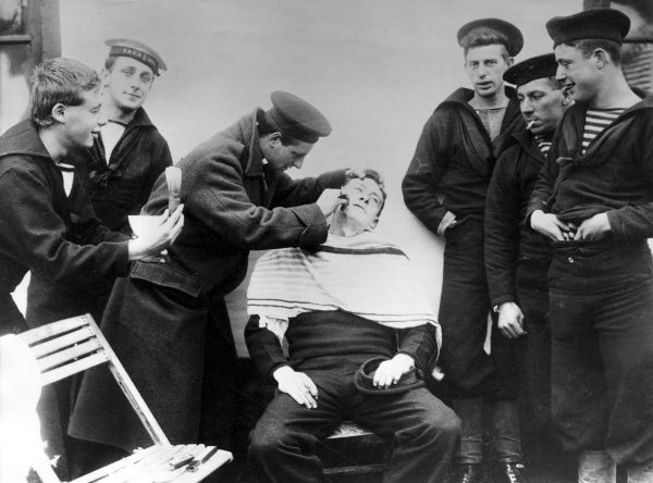 British and French sailors interned in Holland during the First World War. One of them is being given a close shave. Date: 21 November 1914