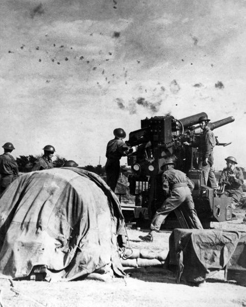British gunners at work beneath flak-filled sky during the Second World War. They are using a Vickers 3.7 inch AA (anti-aircraft) gun on a static mounting. Date: 1939-1945