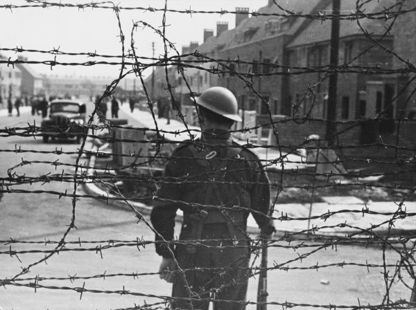 Enemy aliens internment camp in a Northern British town during World War II, a view from outside the compound. The camp is a new Northern Town housing estate which has been totally surrounded by barbed wire and is guarded by sentries