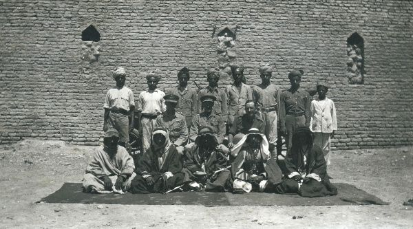 Three British officers (centre) with Indian soldiers (back row) and Arab men (front row) outside a building, somewhere in Iraq