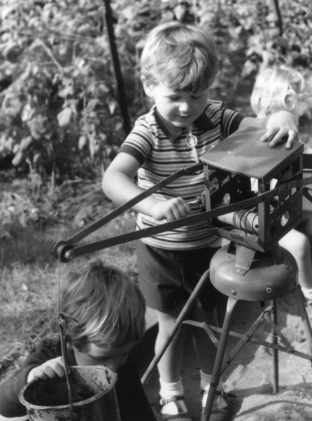 Boys playing with a mechanical bucket toy in a playschool sandpit. Date: 1960s
