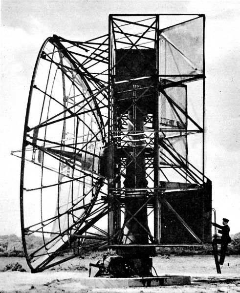 Photograph showing a 'Fighter Direction Aerial system' radar installation in Britain, during the Second World War, c.1945. On the right of the image a technician can be seen climbing the stairs into the control booth of the machine