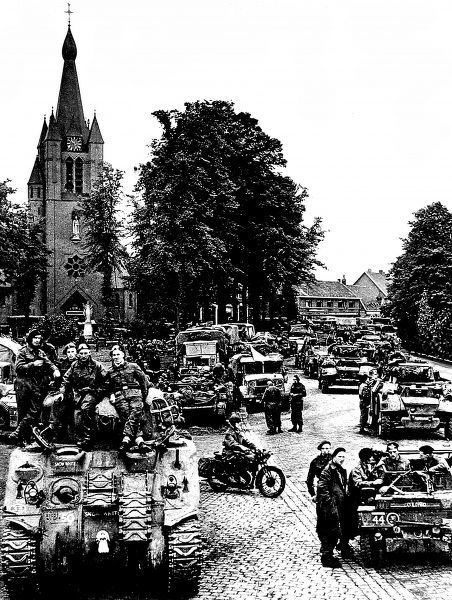 Photograph showing advance units of the British Second Army in the Dutch village of Valkenswaard, September 1944. This was the first settlement in Holland to be liberated. In the foreground one can see a Sherman tank and a motorcycle despatch rider