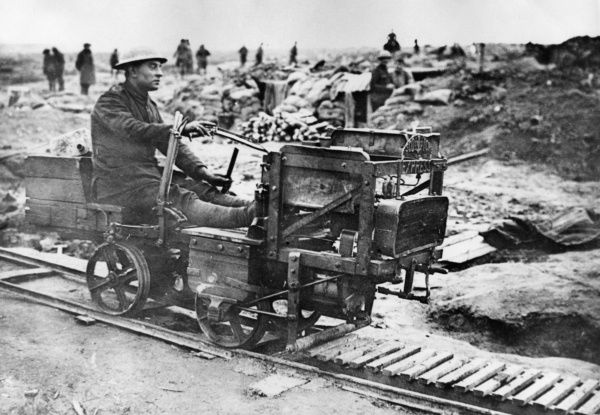 A British soldier riding on a light railway during the First World War. The contraption he is riding is made from parts of an old motor car, and bears the name Scotch Express on the front. Date: 1917