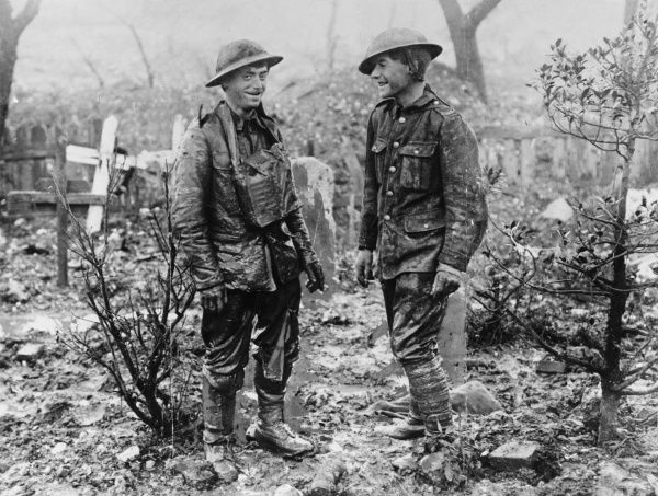 Two British soldiers, muddy and soaked but looking cheerful, stand in the middle of a cemetery, somewhere in the Somme region