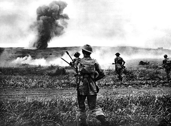 Photograph showing British infantrymen advancing towards enemy positions in Tunisia, North Africa, during 1943. The explosion and smoke in the distance would suggest that these men are advancing with artillery support
