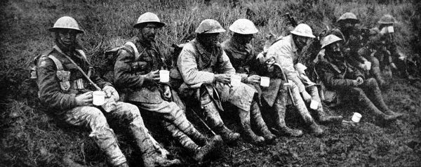 Photograph showing a group of British soldiers, having a rest and a cup of tea after leaving the front line of trenches; Western Front somewhere in France, 1916