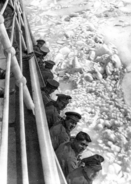Photograph showing a group of British soldiers leaning over the rail on the deck of a transport ship bound for Russia, 1916