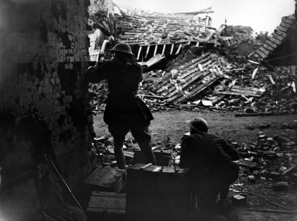 Two British soldiers shooting from behind a brick wall, somewhere on the Western Front during the First World War. Debris from ruined buildings can be seen across the road from them. Date: 1914-1918