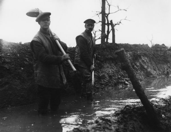 Two British soldiers working in a ditch full of water during the First World War. Date: 1914-1918