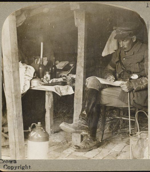 A staff officer from G.H.Q. in a dug-out, studying details before the opening of the British offensive