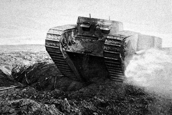 Photograph showing a British tank, perhaps a 'Mark IV Male', on the move over rough ground somewhere in France during the latter part of 1916