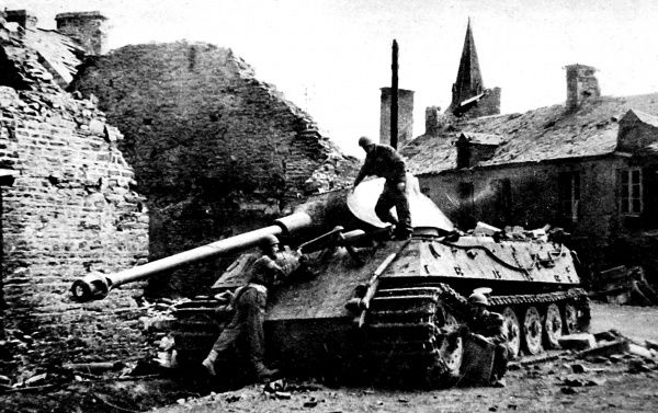 Photograph showing several British soldiers examining an abandoned German Royal Tiger tank, near Falaise, 1944. This heavy tank was reported to weigh 65 tons, with 6-inch armour plating and an 88-mm gun