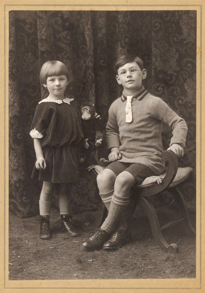A brother and sister, he wearing spectacles and she holding her toy monkey, pose for a studio photograph, inscribed 'With love to Aunt Bertha' on the reverse