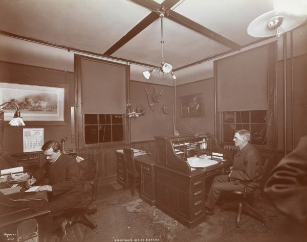 Secretary's Office B.R.T.E.B.A. Interior of the secretary's office of the Brooklyn Rapid Transit Employees Benefit Association; two men are sated at desks, calendar for February 19