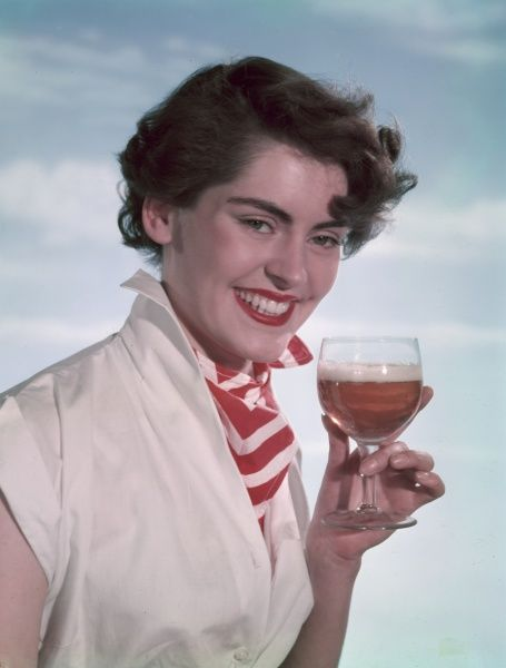 Smiling brunette model, wearing a white cap sleeve blouse with the collar turned up & a red & white chevron pattern cravat, holds up a half empty glass of beer