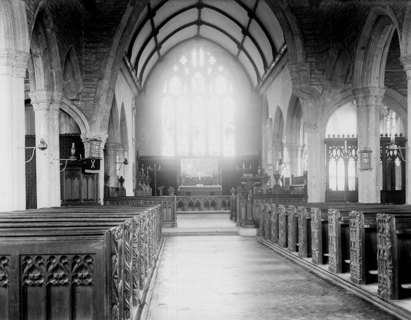 The interior of Buckland Church, near Yelverton, south Devon, England, with an almost paranormal light at the end of the aisle. Date: early 1930s