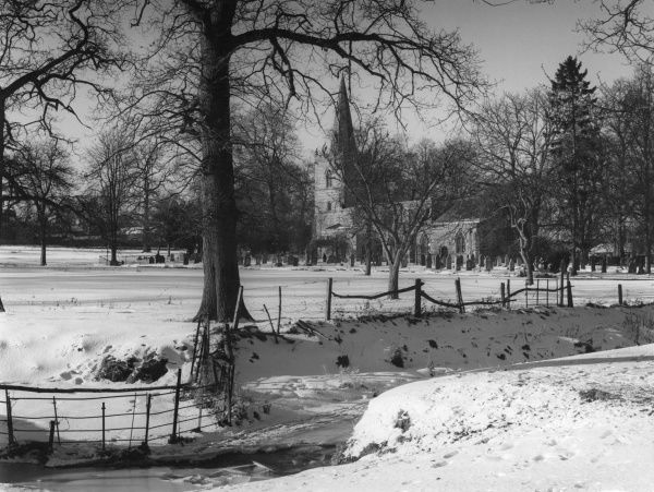 A picturesque winter snow scene, across the frozen Horsetone Brook, to St. Michael's Church, at Bugbrooke, Northamptonshire, England. Date: 1960s