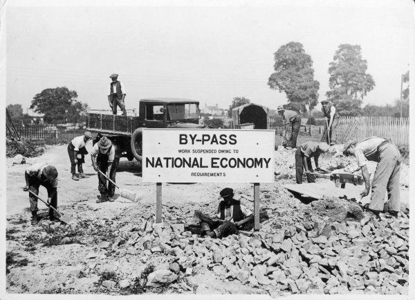 The sign reads 'By-Pass work suspended, owing to National Economy requirements', presumably due to the British Depression. Curiously, these men are still at work