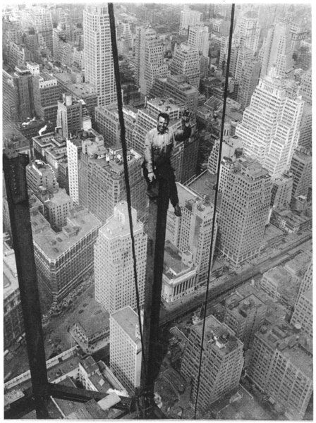 A dizzy perch 350 yards above street level: A New York workman (Carl Russell) engaged on the world's tallest bulding (at the time), the Empire State Building