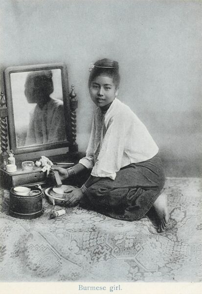 A girl from Burma (modern Myanmar) preparing her make-up in front of a very European-style dressing table mirror, set on the floor