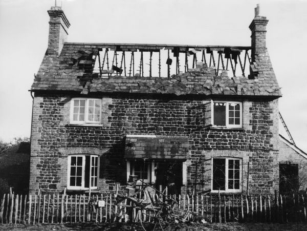 The shell of a burnt-out old stone-built cottage in Kent, England. Date: 1950s