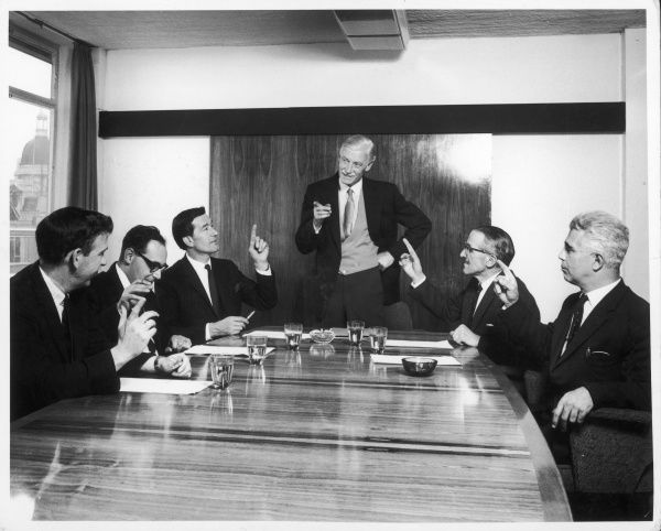 A board meeting takes place. A group of men sit around the board table discussing various issues. Posing for the camera, they all point at the Chair of the meeting