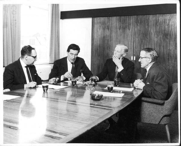 A board meeting takes place. A group of men sit around the board table smoking and discussing various issues