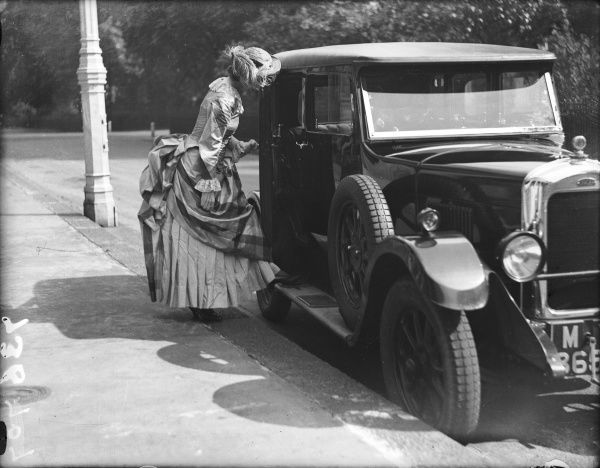 A lady wearing a bustle chats to a 'modern' motor car driver through his car window!