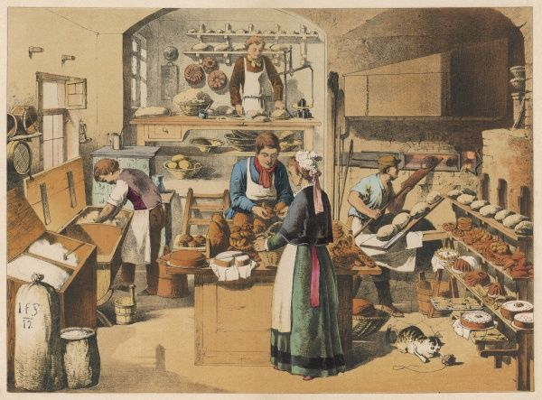 A busy French bakery, with food on display, dough being kneaded on the left, and new loaves being baked on the right