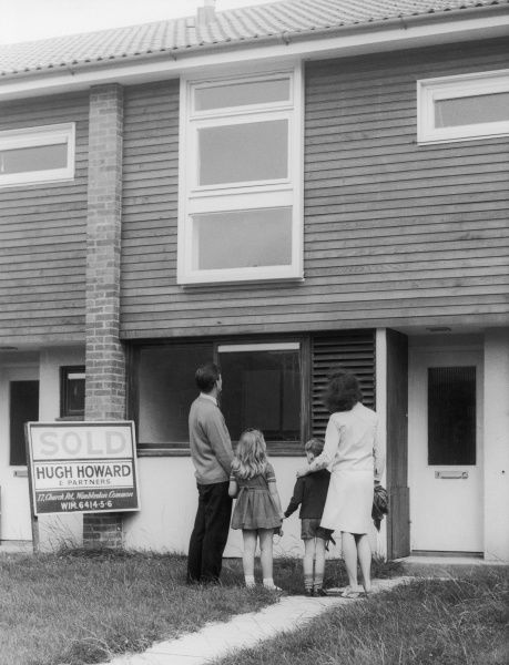 A happy family stand outside their brand new home, 'Sold' by Hugh Howard of Wimbledon Common, London