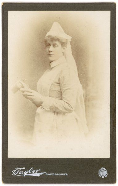 A vignette style photograph of a young nurse resplendent in her starched uniform