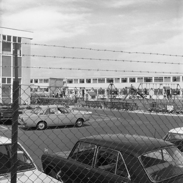 An unusual, unflattering, and slightly humorous view of Camber Sands Holiday Park in East Sussex, England, photographed through the barbed wire fencing, across the car park and looking more like a prison block than a place of leisure