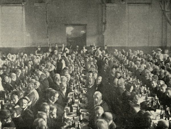 A large party of inmates from the Camberwell workhouse in south east London eating their dinner during their annual outing to Bognor Regis, West Sussex. There is a large bottle of beer at each place setting