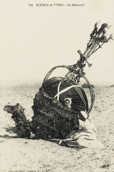 Father and daughter with their camel palanquin (covered litter), used to transport wives and children across the arid desert of southern Algeria, each with a central ventilation shaft, which can double as a tall structure to alert rescuers if