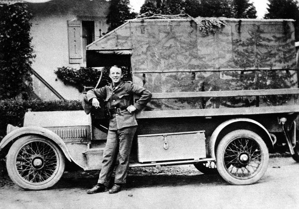 A British soldier poses by his Red Cross ambulance in the Vosges. The ambulance is in camaflague with a landscape of trees painted across its side
