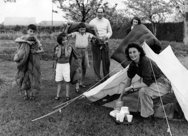 A happy mother emerges from the tent with a tray of unbreakable plastic plates and cups, surrounded by her loving family in this rather idealistic camping scene! Date: early 1950s