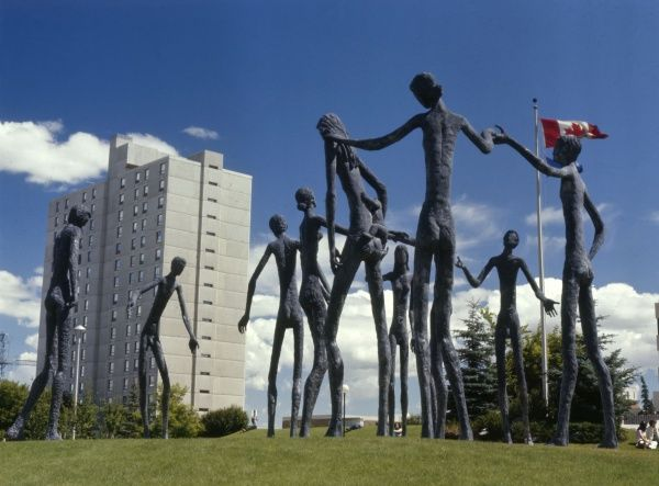Calgary: a block of flats with what appear to be sculptures by Giacometti in the foreground Date: 1985