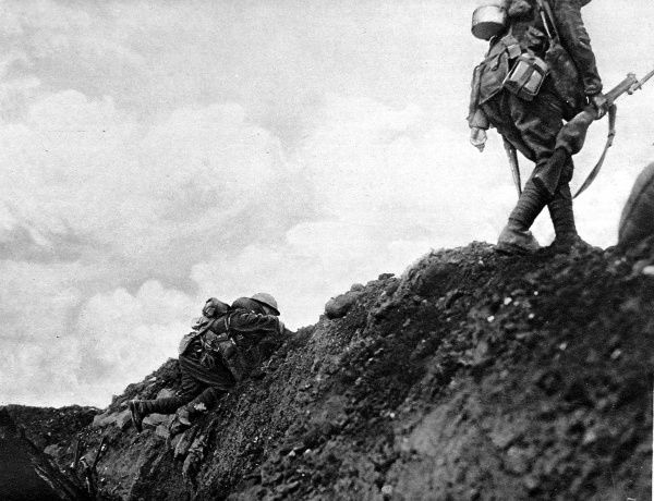 Photograph showing two Canadian troops going 'over the top' to attack German positions on the Somme Front during the First World War, France, 1916