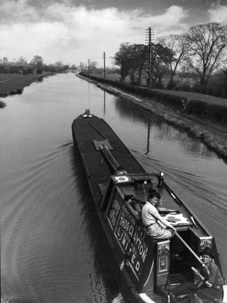 A young couple on a barge on a quiet stretch of the Shropshire Union Canal, near Chester, Cheshire, England. Date: 1950s
