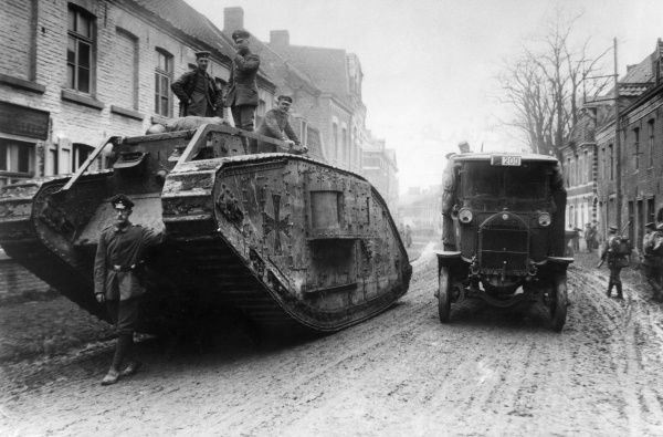 German soldiers accompany a captured British tank through a muddy street in Armentieres, northern France, during the First World War, with a lorry driving alongside.  1918