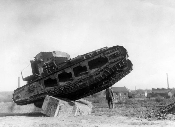 An American photograph of a captured British Whippet tank used by the Germans during the First World War, with a German marking painted on the side. It is perched on a large block of concrete in an open space that looks like an urban bomb site