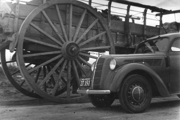 Old and new transport - a 'modern' motor car beside a the wheels of a large horse cart! Date: 1930s