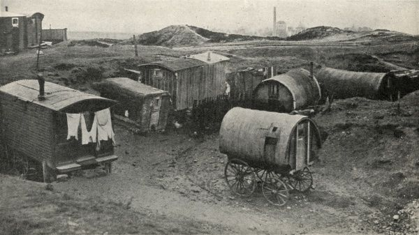 An assortment of caravans, some with wooden wheels and others having lost their wheels, near a quarry in County Durham. Date: circa 1936