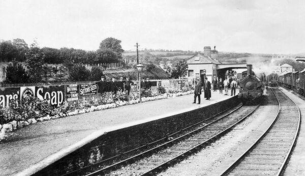 View of a platform of Cardigan Railway Station on the Great Western Railway, Cardiganshire, South Wales, with flowerbeds and tinplate advertisements for Pears Soap and Sutton Seeds. A steam train stands waiting at the platform, and most of the people